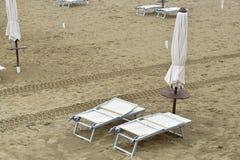 Parasoles y sillas de cubierta en la playa durante una tormenta en los mares agitados Fotografía de archivo libre de regalías