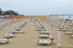 Parasoles y sillas de cubierta en la playa durante una tormenta en los mares agitados Fotos de archivo