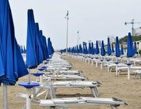 Parasoles y sillas de cubierta en la playa durante una tormenta en los mares agitados Imagen de archivo