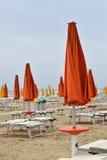 Parasoles y sillas de cubierta en la playa durante una tormenta en los mares agitados Foto de archivo