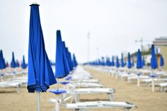 Parasoles y sillas de cubierta en la playa durante una tormenta en los mares agitados Imagen de archivo libre de regalías