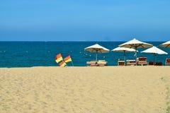 Parasoli con le chaise-lounge sulla spiaggia vicino all'oceano blu con le bandiere fotografia stock