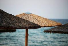 Parasoli di legno del sole alla spiaggia dal mare Fotografie Stock