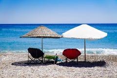 Parasoli e sdrai sulla spiaggia dal mare fotografia stock