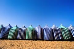 Parasoller i strand på sommar mot blå himmel Royaltyfria Bilder