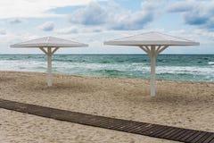 Parasoller på sandstranden royaltyfri bild