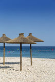 Parasols at the beach in front of blue ocean Royalty Free Stock Image