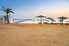 Parasols on the beach of Red Sea in Hurghada at sunrise. Egypt Stock Images