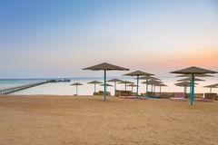 Parasols on the beach of Red Sea in Hurghada at sunrise. Egypt Stock Photos