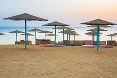 Parasols on the beach of Red Sea in Hurghada at sunrise. Egypt Royalty Free Stock Images