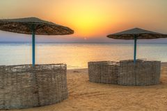 Parasols on the beach of Red Sea in Hurghada at sunrise. Egypt Royalty Free Stock Photos