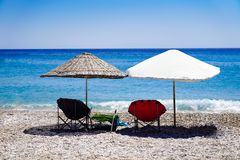 Parasols and deck chairs on the beach by the sea stock photography