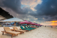 Parasols on empty beach at Sunrise in Bali Stock Image