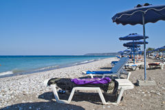 Parasols en sunbeds op het strand stock fotografie