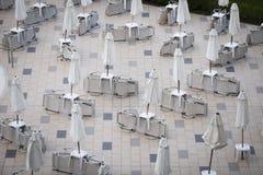 Parasols et chaises de jardin fermés pendant la saison photographie stock libre de droits
