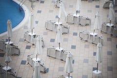 Parasols et chaises de jardin fermés pendant la saison photographie stock