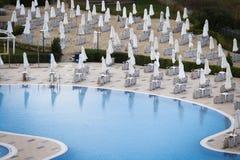 Parasols et chaises de jardin fermés pendant la saison images stock