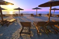 Parasols et lits pliants sur la belle plage sablonneuse en été Photos stock