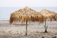 Parasols at Maleme beach on Crete. Tropical parasols on empty Maleme beach of Crete, Greece Stock Photography