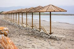 Parasols at Maleme beach on Crete. Tropical parasols on empty Maleme beach of Crete, Greece Royalty Free Stock Images