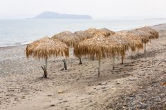 Parasols at Maleme beach on Crete. Tropical parasols on empty Maleme beach of Crete, Greece Royalty Free Stock Photography