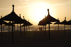Parasols of Mallorca in sunset. Beautiful sunny beach in Palma de Mallorca Royalty Free Stock Images