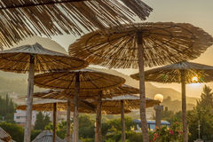 Parasols in morning sun. Parasols made of the dried leaves of palm leaves. Main colors are pastel orange, gold and warm green. Sun is rising behind the mountains Stock Images