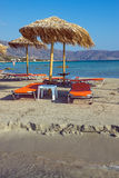 Parasols and sun loungers. At a beautiful beach in Greece royalty free stock photos