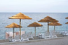 Parasols and sun loungers. On the deserted Istrian beach Royalty Free Stock Photography