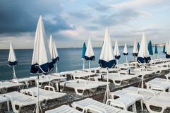 Parasols and sunbeds 2. A picture of an empty morning beach in Nice, Cote d' Azur, France Royalty Free Stock Photo