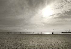 Parasols on vast empty winter beach. In Mallorca, Balearic islands, Spain Royalty Free Stock Photography
