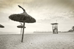 Parasols on winter beach. In vintage retro monotone color in Mallorca, Balearic islands, Spain Stock Image