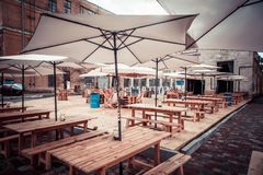 Parasols on wooden tables. In the cafe on the street Stock Photos