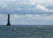 Parasurfing on Carlingford Lough. Parasurfer flies across the water towards Haulbowline Lighthouse, on Carlingford Lough, Northern Ireland Stock Photography