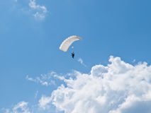 Paratrooper. Parachutist with a white parachute flying among the clouds Royalty Free Stock Images