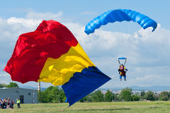 Paratrooper carrying the flag at the Romanian Air Show. A paratrooper descending, carrying the Romanian national flag, at the Romanian Air Show, which took place stock image