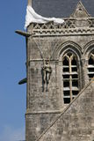 Paratrooper memorial. Dummy US paratrooper hanging from a church in Ste Mere Eglise, France stock images