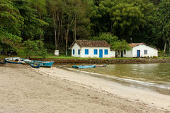 Paraty Fisherman Houses and Boats. A tranquil beach in Paraty, Rio de Janeiro, with some fisherman wood colorful boats and two typical historical portuguese stock photo