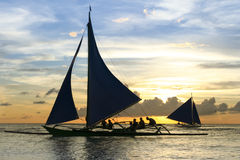 Paraw outrigger sunset tour boracay philippines. Tourists onboard paraw traditional outrigger sailing boats at sunset tours along the coast of boracay island in Stock Image