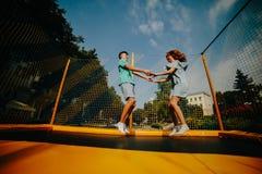 Parbanhoppning på trampolinen i parkera Fotografering för Bildbyråer