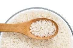 Parboiled rice and wooden spoon in glass bowl on white background. Royalty Free Stock Image
