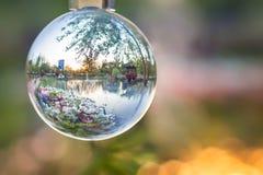 Parc asiatique de ville avec le lac, les fleurs de fleur et le pavillon vus une boule de verre cristal, horizontale photos stock