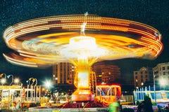 Parc d'attractions et carrousel la nuit, long concept de plaisir de carnaval de divertissement de tache floue de mouvement d'expo images stock