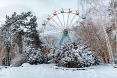 Parc d'hiver et attraction de cercle de ferris Belle scène blanche de neige avec des arbres Photographie stock