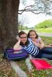 Parc de dessous décontracté d'arbre de filles d'amies de soeur après école Photographie stock libre de droits