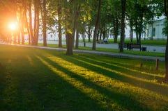 Parc et touristes de Veliky Novgorod Kremlin marchant le long des allées de parc au coucher du soleil Image libre de droits