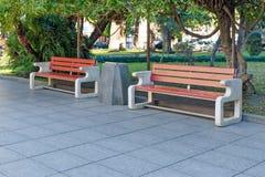 Parc ou rue avec les arbres verts et tuile de ville - deux bancs ordonnés faits de béton et bois, entre la poubelle de déchets photo libre de droits