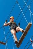 Parc s'élevant de corde d'aventure - une jeune femme dans la vitesse protectrice passe la voie sur un simulateur de corde alpinis Photo stock