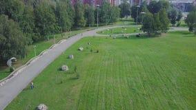 Parc vert et ses vastes pelouses une journée de printemps ensoleillée clip Antenne de bourdon de vol d'un parc de ville avec le c Photographie stock