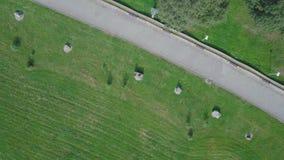Parc vert et ses vastes pelouses une journée de printemps ensoleillée clip Antenne de bourdon de vol d'un parc de ville avec le c Image stock